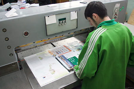 An operator setting up a guillotine cutter
