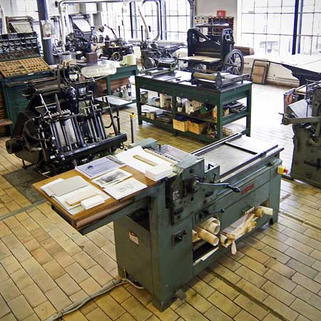 A small press for printing proofs with a Heidelberg Windmill in the background