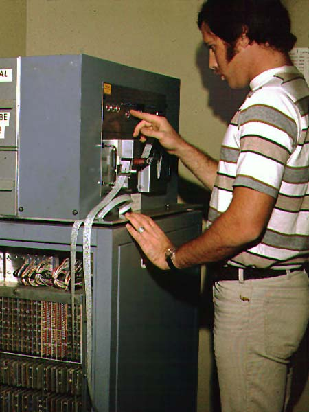 A prepress operator loading paper tape into a typesetter