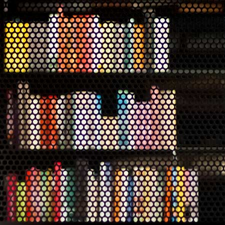 Books become a blurred pattern behind a steel curtain
